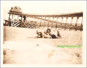 Barbat cu palarie de soare, impreuna cu sotia, pe plaja in perioada interbelica