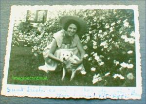 Doamna cu palarie de soare in gradina cu flori